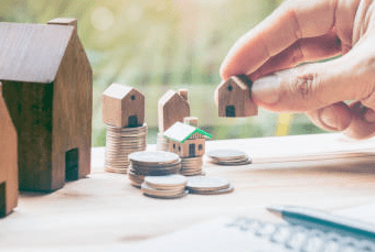 Person Placing Tiny Houses on Quarters to Represent Landlords With Rental Properties | CloudTax PRO
