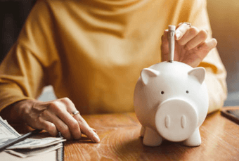 Person Placing Money in a Piggy Bank Representing People With Investment Income | CloudTax PRO